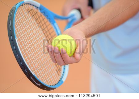 Closeup of man poised to serve at tennis