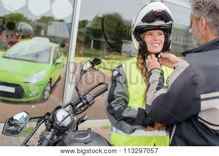 man putting helmet on his student