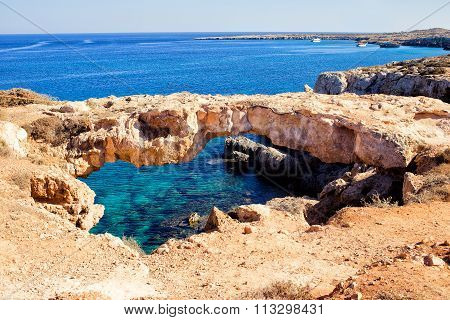 Natural bridge in Cavo Cape Greco, at National Forest Park