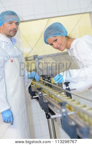 Man and woman working on factory production line