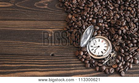 Old pocket watch lying on the coffee beans scattered on the old wooden table. Focus on dial