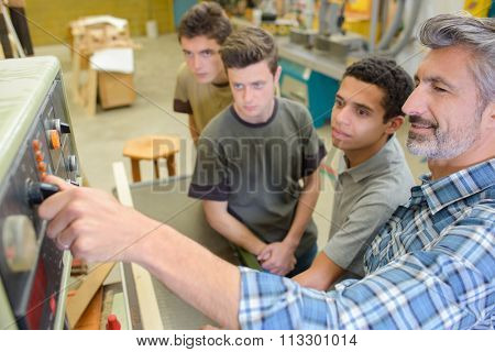 Man showing how to start machine in workshop