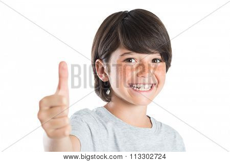Closeup of smiling little boy showing thumb up gesture isolated on white background. Portrait of happy cute boy showing thumb up and looking at camera. Kid giving you thumbs up.