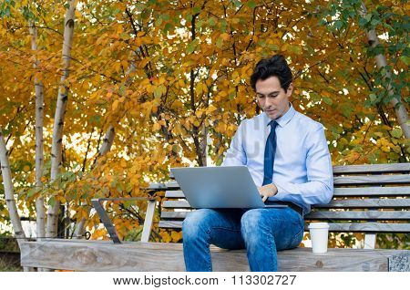 Businessman using laptop in the park in an autumn day with. Young man sitting on the park bench with laptop on his lap and checking the email. Freelancer man sitting on bench and working on computer.