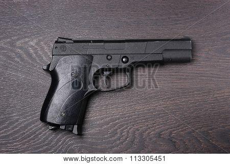 Black Pneumatic Pistol Against A Dark Background.