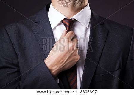 Man in a suit fixing his tie on grunge background