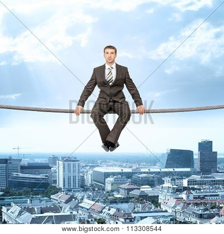 Businessman sitting on rope