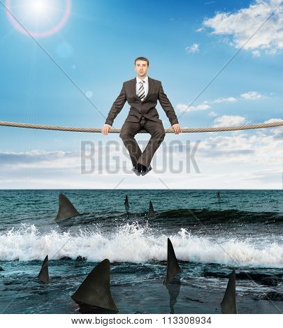 Businessman sitting on rope
