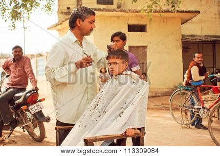 Unidentified Boy Of Preschool Age Cuts By The Barber On The Street Among The People