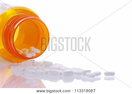med bottle spilling pills on reflective surface
