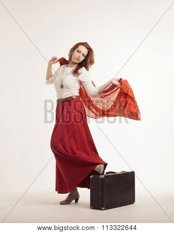 young woman in skirt dancing with a red handkerchief and suitcase
