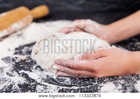 Baking preparing background. Female hands knead dough on the worktop.