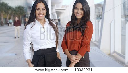Two Adorable Women Standing at Promenade in Malaga Pier and looking at camera  they wearing formal business elegant clothes  smiling