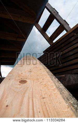 pine board against a pile of boards and a ladder