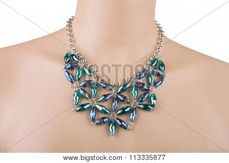 Silver statement necklace on a mannequin with blue and green rhinestones. A rhinestone or diamante is a diamond simulant made from rock crystal, glass or acrylic