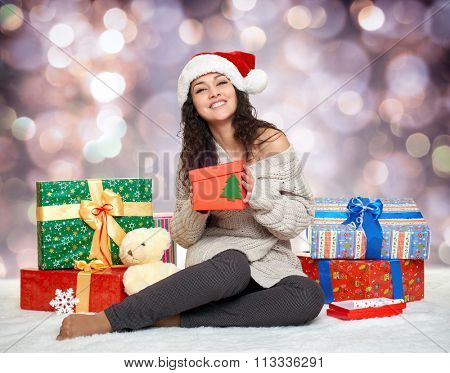 beautiful young girl in santa hat with gift boxes, colorful holiday  bokeh background