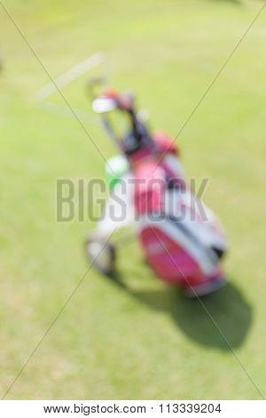 Blurred Photo Of Golf Bag Leaving On Green Field During The Golf Match.