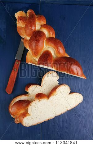 sweet bread : golden challah cuts over blue wooden plate