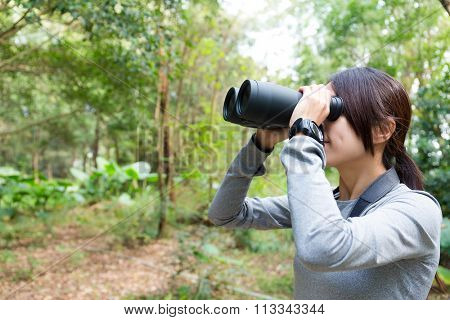 The side profile of Woman looking though binocular