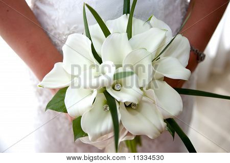 Bride holding wedding bouquet of white flowers and crystals Stock photo