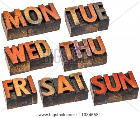 a set of 7 days of week (first 3 letter symbols) in isolated vintage wood letterpress printing blocks stained by color inks