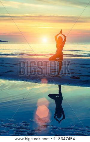 Silhouette young woman practicing yoga on sea beach at surrealistic sunset.