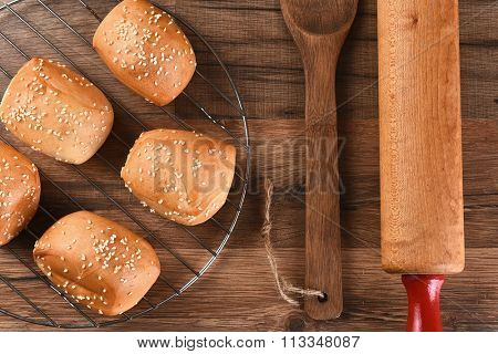 Overhead view of a rack of Sesame seed dinner rolls next to a wooden spatula and rolling pin.