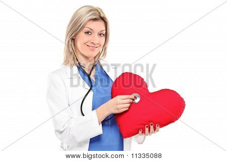 Smiling Doctor Examining A Red Heart Shaped Pillow With A Stethoscope