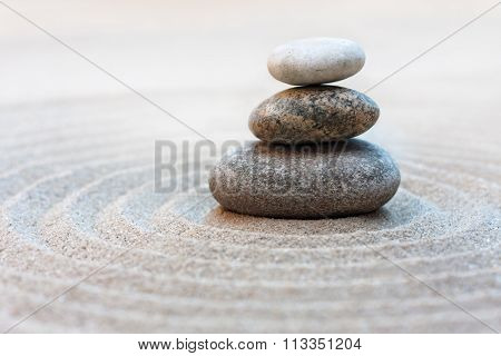 zen garden with stone stack on sand with circle grooves