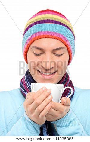 Hombre sonriente que llevaba un sombrero y bufanda con una taza de té