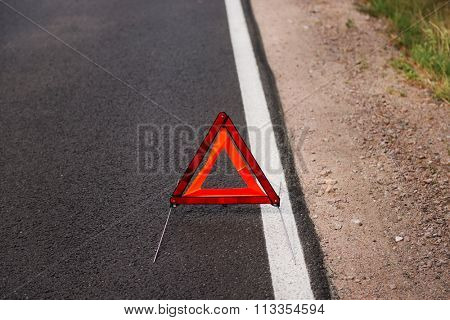 One red warning triangle on a road.