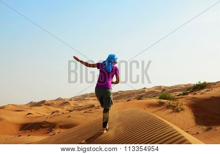 Woman on top of a sand dune in Oman