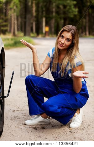 Female mechanic changing tire with wheel wrench.