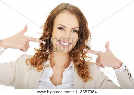 Happy business woman shows us her teeth.