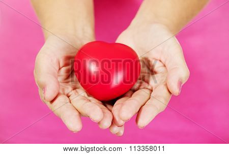 Old woman holding red toy heart.