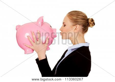 Young business woman kissing a piggybank.