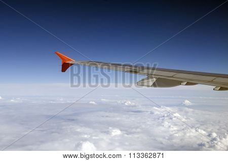 Above the clouds in the sky. Wing of the Airbus above the clouds.