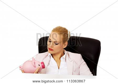 Angry business woman looking for her piggybank and sitting behind the desk.