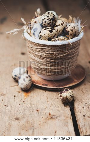 Quail eggs in Easter pot on a wooden table