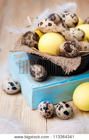 Brown bowl with quail I yellow chicken eggs. Set Easter eggs on a wooden table.