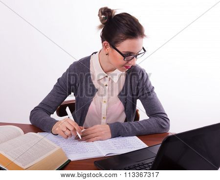 Young beautiful female teacher sitting at a table and reads the book and makes notes in a notebook