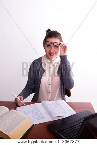 Young beautiful female teacher sitting at a table and reads the book