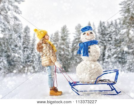 happy child girl plaing with a snowman on a snowy winter walk. child rolls a snowman on a sled
