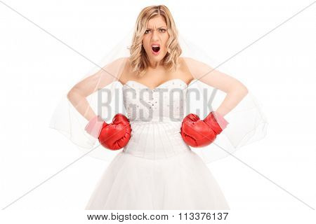 Angry bride in a white wedding dress and red boxing gloves looking at the camera isolated on white background