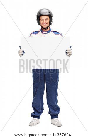 Full length portrait of a young male car racer holding a blank banner and looking at the camera isolated on white background