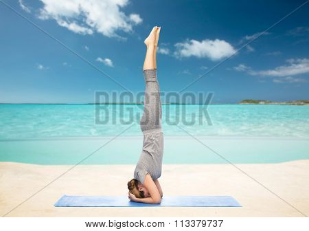 woman making yoga in headstand pose on beach