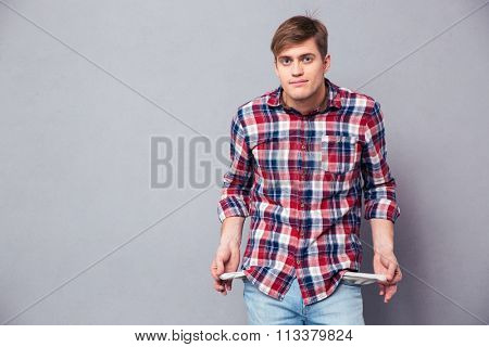 Poor handsome young man in checkered shirt and jeans showing empty pockets over grey background