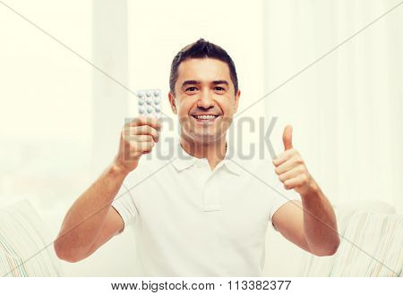 happy man with pack of pills showing thumbs up