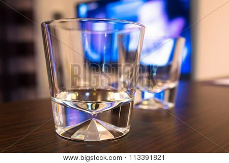 Empty whiskey glasses at the tv