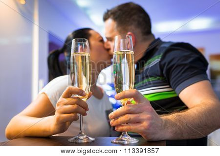 Couple on the romantic date with flutes of champagne